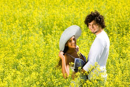 Image of dates standing close to each other and looking at camera in the field full of yellow flowers  photo