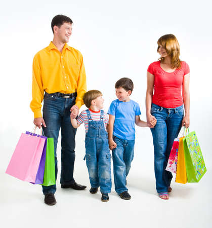 Photo of friendly family walking with shopping bags over white background photo