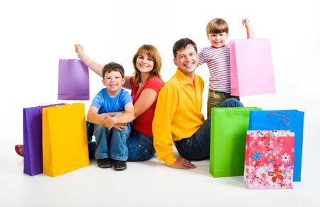 ni�os de compras: Imagen feliz de los padres y sus dos hijos sentado en el estudio con bolsas de la compra por cerca de