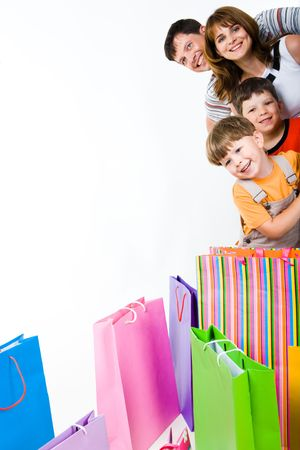 shopping man: Image of glad family looking at camera with smiles with bags in front of them