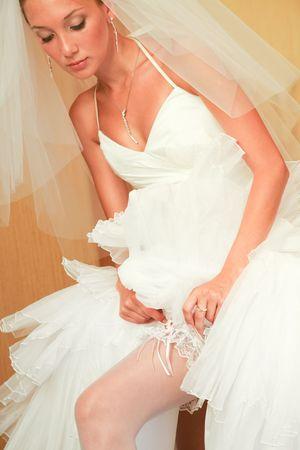 dressing gown: Portrait of elegant bride setting the garter straight on her leg while preparing for wedding