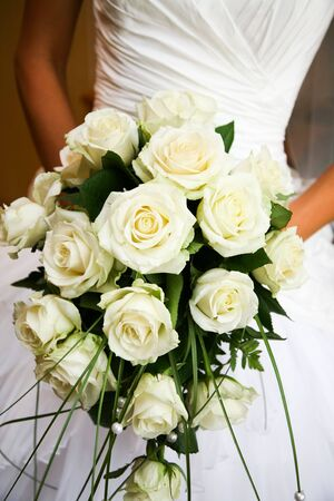 Close-up of white rose bouquet decorated with pearl beads in bride's hands  Stock Photo