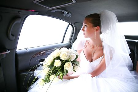 wedding portrait: Portrait of beautiful bride with rose bouquet in hands sitting in the car and looking aside