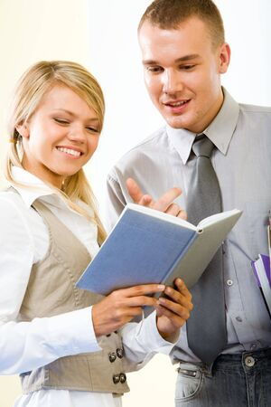Portrait of smart guy pointing at notebook and explaining something to smiling girl photo