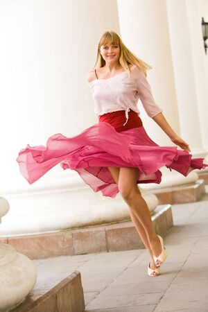 tanktop: Portrait of young girl wearing fashionable tanktop and skirt walking playfully along white columns Stock Photo