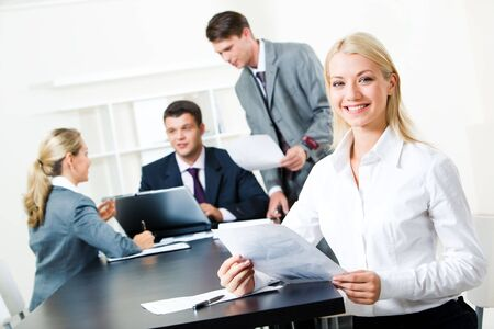 competitive business: Portrait of successful businesswoman sitting at the table in a working environment