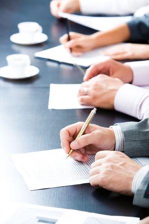 pencil paper: Close-up de la l�nea de las manos con las plumas m�s papeles sobre la mesa Foto de archivo