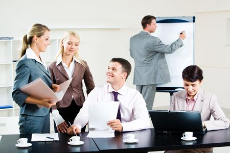 working: Image of business group discussing new project during break in the office  Stock Photo
