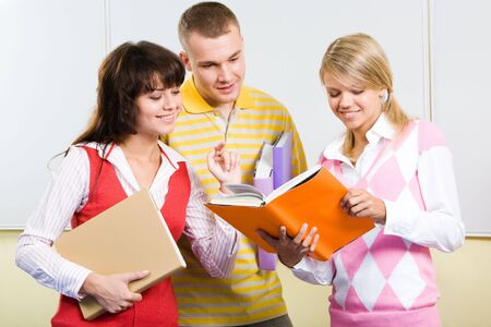 Photo of teenagers looking into textbook held by pretty girl and interacting in classroom photo
