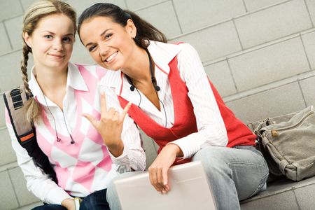 Portrait of two happy girls sitting on staircase and looking at camera photo