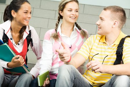 Image of three attractive students chatting before lesson photo