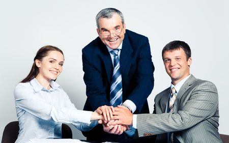 Photo of three partners putting their hands on the top    photo