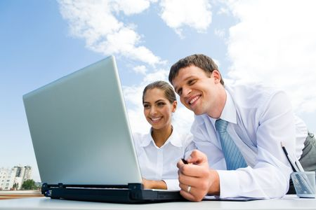 somewhere: Photo of joyful colleagues watching into laptop monitor with happy smiles somewhere in the city Stock Photo