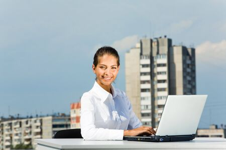 Successful business lady working with laptop somewhere outside and looking at camera photo