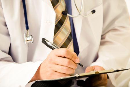 stethoscope: Close-up of doctor's hands holding pen over paper ready to prescribe pills to patient