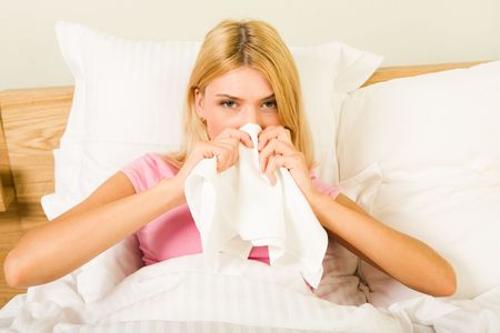 catarrh: Photo of sick woman sitting in bed with tissue and blowing her nose into it