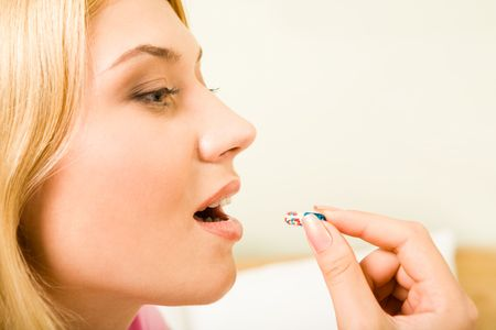 Profile of young woman holding pill by her mouth before taking it Stock Photo - 3545165