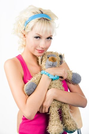 Portrait of blonde girl holding teddy bear in hands and looking at camera photo