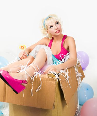 fashion doll: Image of pretty young girl sitting inside box and holding lollypop while looking upwards