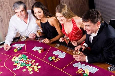 people partying: Portrait of people sitting at the table and gambling