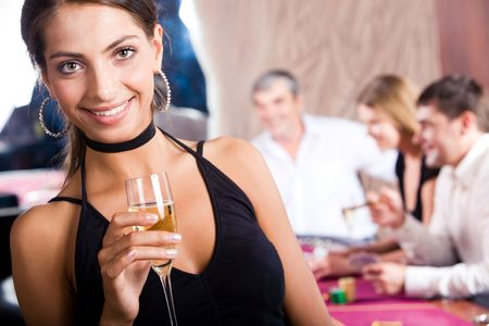 Portrait of pretty girl in black evening dress holding glass of champagne with her friends behind photo