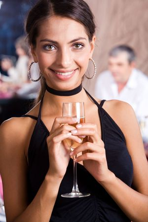 Portrait of fashionable woman with glass of champagne in hands looking at camera happily photo