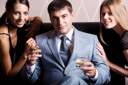 smoking cigar: Portrait of handsome man in grey suit sitting with whisky and cigar between two pretty women in casino