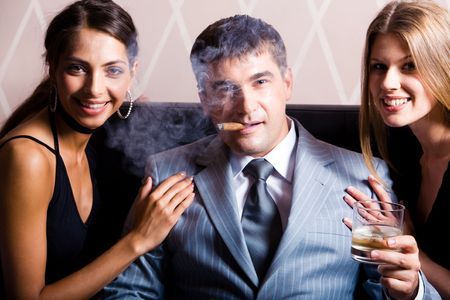 smoking cigar: Portrait of successful man smoking a cigar holding whisky with pretty women near by