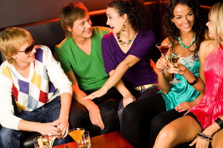 Portrait of five happy people sitting on the sofa and interacting at evening-party  Stock Photo - 3545357