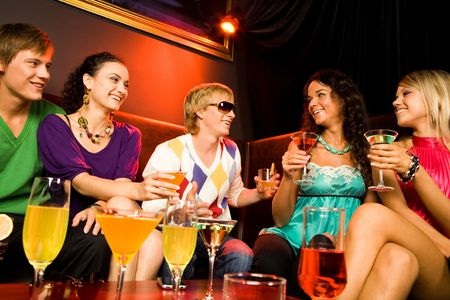 Portrait of friends sitting on the sofa and holding the cocktails in the nightclub Stock Photo - 3545350
