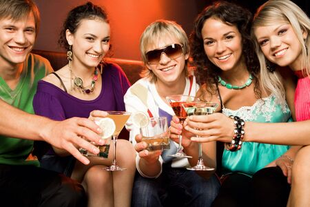 Portrait of young people touching the glasses with each other in the nightclub Stock Photo - 3545351