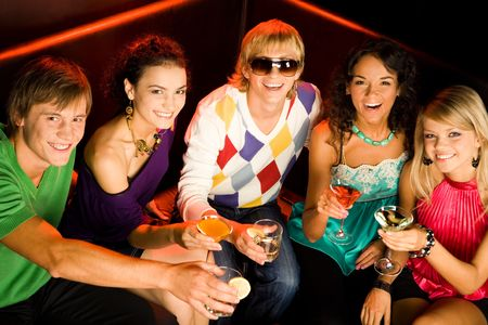 Portrait of five smiling teens holding cocktails and sitting on the sofa Stock Photo - 3545354