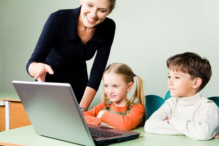Image of two pupils looking at laptop monitor while teacher pointing at it photo