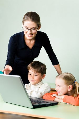 Photo of elegant teacher explaining new topic by pointing at laptop monitor while children looking at it photo