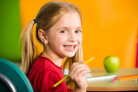 diligent: Portrait of diligent schoolgirl with pencil looking at camera during lesson Stock Photo