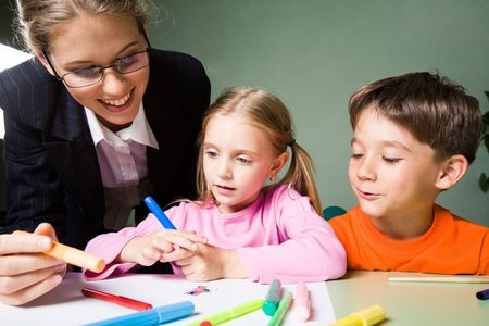 Image of smiling teacher holding highlighter and looking at girl�s picture while cute boy expressing his opinion photo