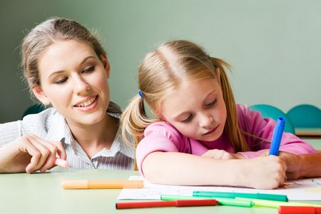 diligent: Portrait of diligent girl drawing something under tending of her teacher Stock Photo