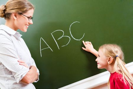 spelling: Image of smart girl pointing at letter on blackboard and looking at her teacher with smile