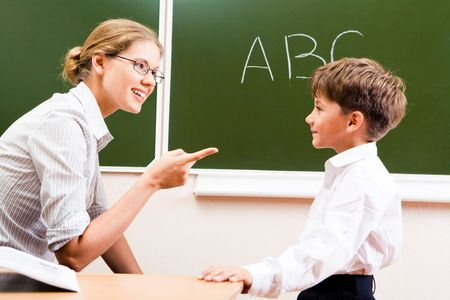 sled: Portrait of confident teacher explaining grammar to schoolchild who looking at her attentively Stock Photo