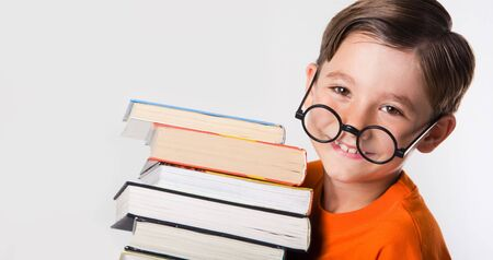 one little boy: Portrait of cute boy wearing circle glasses and holding books while looking at camera Stock Photo