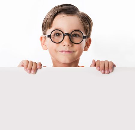 Face of youthful boy in glasses looking from behind white partition