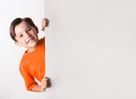 Image of laughing lad looking from behind white vertical partition Stock Photo - 3556563