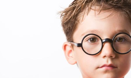 close up eyes: Close-up of smart guy in preschool age looking at camera through glasses