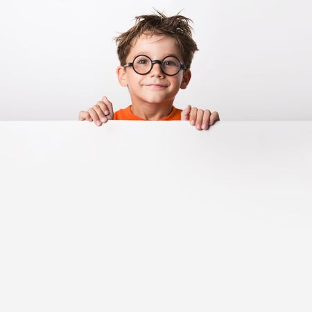 Photo of positive schoolkid behind partition looking at camera with smile Stock Photo - 3556586