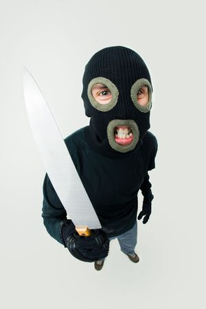 Fish-eye shot of gangster wearing black balaclava with knife in hand  photo