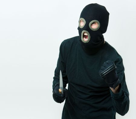 Portrait of felon in balaclava with knife in gloved hand photo