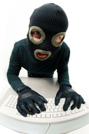 delinquent: Image of criminal in balaclava pressing buttons of keyboard Stock Photo