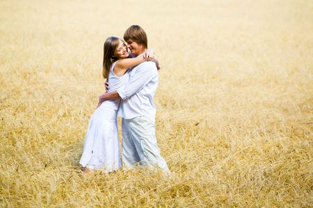 Photo of happy couple embracing in wheat field  photo