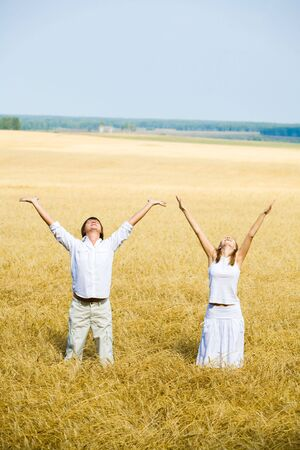 View of happy people raising their hands standing in the field Stock Photo - 3688870