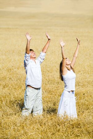View of happy people raising their hands standing in the field Stock Photo - 3688867